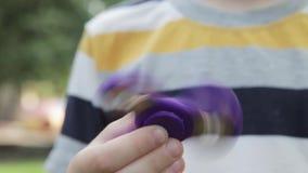 一个小男孩使用与锭床工人 男孩在他的手上转动一名锭床工人 股票视频