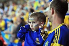 一个小男孩关闭他的从喧闹声的耳朵在Th 库存图片