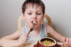 一个小男孩吃被烘烤的鸡用从泥罐的土豆 库存图片