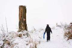 一个小男孩在一条多雪的道路去 库存照片