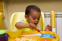 一个小男孩在儿童` s椅子和吃坐 库存图片