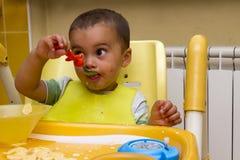 一个小男孩在儿童` s椅子和吃坐 图库摄影