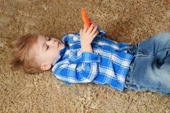 一个小男孩在地毯说谎并且充当电话 使用智能手机的小男孩 库存照片