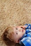 一个小男孩在地毯说谎并且充当电话 使用智能手机的小男孩 图库摄影