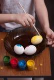 一个小男孩在复活节、五颜六色的油漆和刷子的前夕绘鸡蛋, 图库摄影