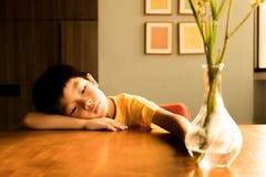 一个小男孩在家坐木桌在阳光下在充满偏僻的感觉的晚上 他没有使用的朋友 免版税图库摄影
