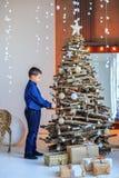 一个小男孩在家装饰一棵圣诞树 概念愉快的Chr 库存照片