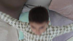 一个小男孩在床上在一种好心情躺下并且准备睡觉 股票视频