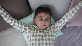 一个小男孩在有的床上的早晨醒一种好心情 股票视频