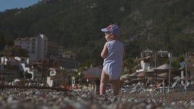 一个小男孩在海滨站立,投掷小卵石入水,慢动作 股票录像