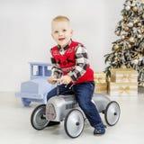 一个小男孩在玩具汽车乘坐 概念愉快的圣诞节,新的Ye 库存照片