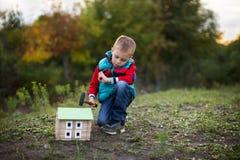 一个小男孩在秋天森林收集一位木房子设计师 免版税库存照片