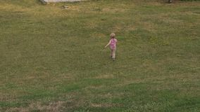 一个小男孩在绿草跑在公园,他跑在小山下 股票视频