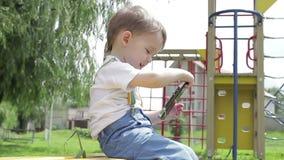 一个小男孩坐使用与智能手机的长凳在操场微笑 股票录像