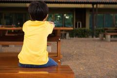 一个小男孩坐充满偏僻的感觉的木桌在学校 等待他的父母的他在学校以后 库存图片