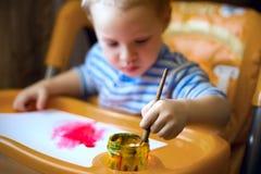 一个小男孩坐在孩子桌上,拿着刷子,油漆,油漆 库存照片