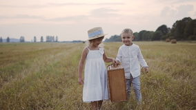 一个小男孩帮助一个女孩佩带在一件白色礼服的秸杆手提箱 在领域的儿童步行 日落 股票视频