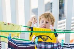 一个小男孩帮助她的母亲挂掉电话穿衣 库存图片