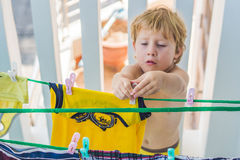 一个小男孩帮助她的母亲挂掉电话穿衣 库存照片