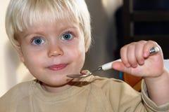 一个小男孩拿着一把匙子并且看直接入与大蓝眼睛的照相机 免版税库存照片