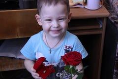 一个小男孩拿着一朵红色玫瑰和一个箱子有一只金戒指的在他的手上 库存图片