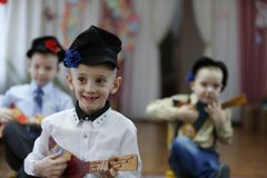 一个小男孩播放俄式三弦琴 免版税库存照片