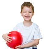 一个小男孩播放球和笑 免版税图库摄影