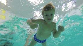 一个小男孩潜水入水池,游泳在水面下与她的开放和看照相机的眼睛 股票录像