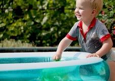 一个小男孩用水使用在一个可膨胀的水池附近 夏天和家庭假日 愉快的童年 免版税库存图片