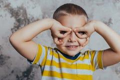 一个小男孩由摆在一个灰色混凝土墙前面的眼睛交叉他的双臂 佩带黄色的一个微笑的孩子的画象 免版税库存图片