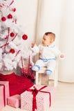 一个小男孩的画象在家在圣诞树附近 免版税库存照片