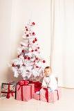 一个小男孩的画象在家在圣诞树附近 免版税库存图片