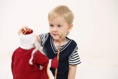 一个小男孩的画象有一个玩具的在他的手上,轻的背景 图库摄影