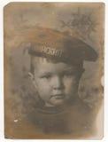 一个小男孩的画象照片他的盖帽的有题字波罗地舰队的 图库摄影