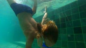 一个小男孩的Ultrahd慢动作水下的射击在水池学会如何游泳 小孩男孩潜水入水池并且拉扯 股票录像