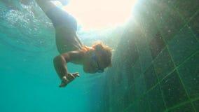 一个小男孩的Ultrahd慢动作水下的射击在水池学会如何游泳 小孩男孩潜水入水池并且拉扯 影视素材