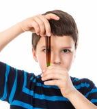 一个小男孩看有色的液体的一个烧瓶 图库摄影