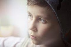 一个小男孩看窗口并且是哀伤 轻的视窗 免版税库存照片