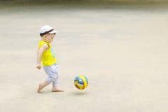 一个小男孩踢橄榄球,球飞行 活跃孩子在与球的夏天 免版税图库摄影
