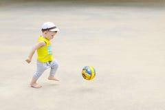 一个小男孩踢橄榄球,球飞行 活跃孩子在与球的夏天 库存照片