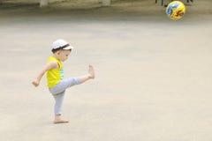 一个小男孩踢橄榄球,球飞行 活跃孩子在与球的夏天 免版税库存图片