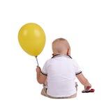 一个小男孩转回去与一个大黄色气球 支付玩具汽车的逗人喜爱的孩子隔绝在白色背景 图库摄影