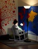 一个小男孩,坐在一把摇椅,读,并且灯在他上发光 墙壁-世界和橙色乐趣树的地图 免版税库存图片