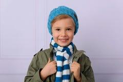 一个小男孩,微笑,看照相机,在蓝色焰晕 免版税库存照片