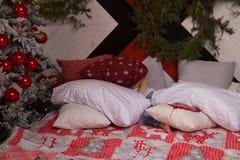 一个小男孩,跳跃在床上的孩子,在枕头中,在新年树附近,在牛仔裤和白色T恤 免版税图库摄影