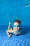 一个小男孩说谎在水面下在水池的底部,看我并且广泛微笑 从水下面的看法 特写镜头 免版税库存照片