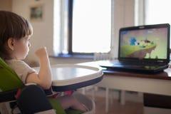 一个小白肤金发的在膝上型计算机的男孩观看的动画片,当坐儿童` s椅子时 库存图片