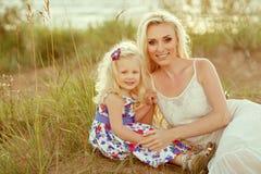 一个小白肤金发的女孩和她的妈妈在沙子和gras微笑着 免版税图库摄影