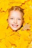一个小白肤金发的女孩的面孔秋叶的 库存照片