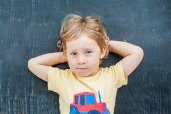 一个小白肤金发的孩子男孩的顶视图有空间文本的和标志的在老木背景 混乱的,突发的灵感概念 图库摄影